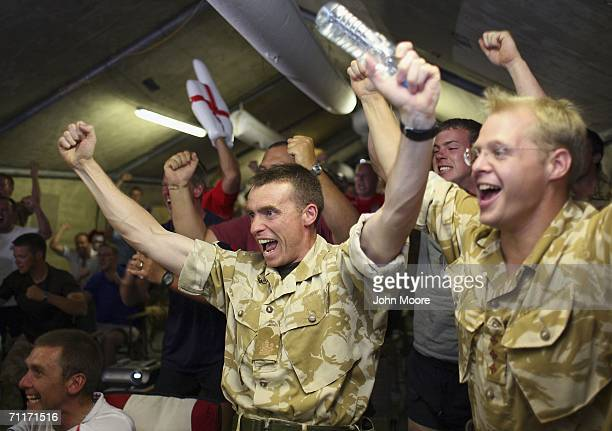 British soldiers including RSM John Landy and Capt Joe Chestnutt cheer at their base after England scored their only goal against Paraguay during...