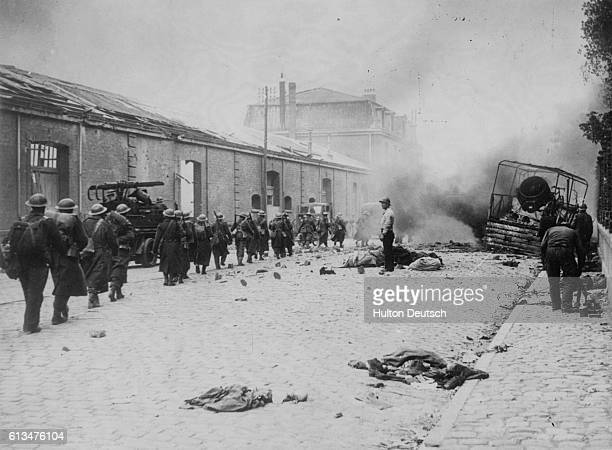 British soldiers march through a street in Dunkirk as it is heavily bombed in an attempt by the Germans to take the town before the evacuation of the...