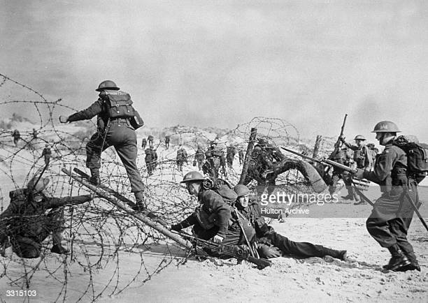 British soldiers negotiating a barbed wire defence during a seashore invasion exercise.
