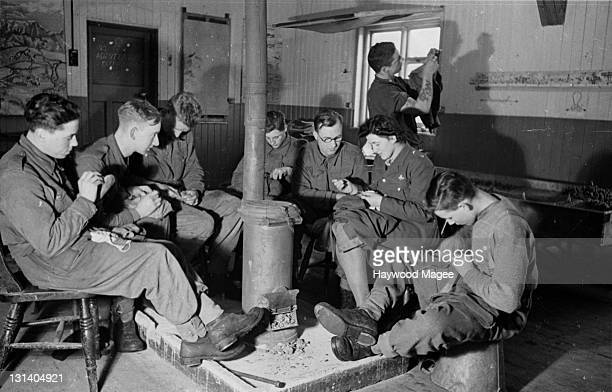 British soldiers of the Eastern Command gatherd around a stove are taught how to sew and mend their clothes by a volunteer from the Auxiliary...