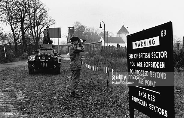 British soldiers on border patrol watch as East Germans build an extention of the Berlin wall | Location Border of West Berlin West Germany