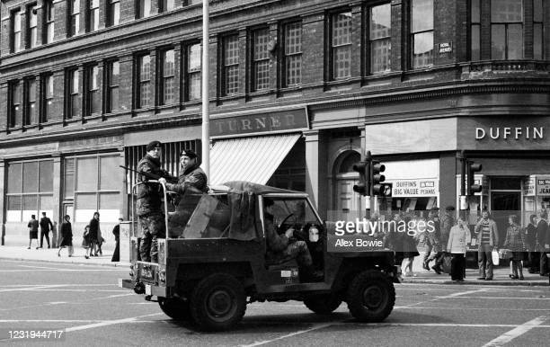 British soldiers patrol the streets of Belfast in an open-top Land Rover with doors removed and riot shields visible in the rear, Royal Ave, Belfast,...