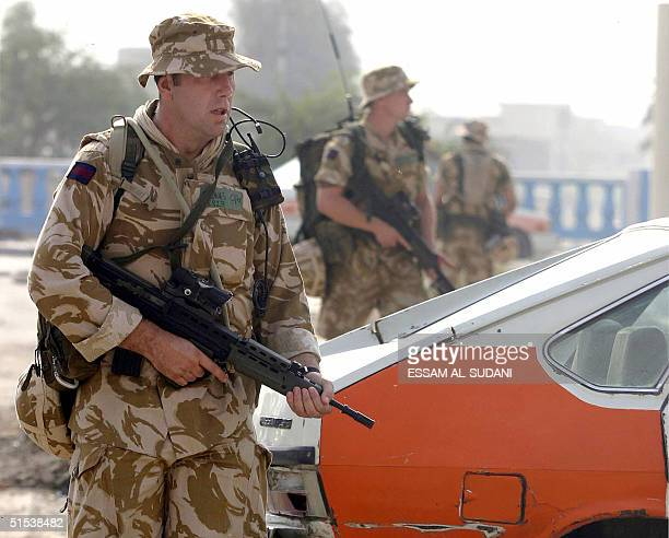 British soldiers patrolling the streets of the southern city of Basra 500 kms south of Baghdad walk past a taxi 22 October 2004 Britain agreed...