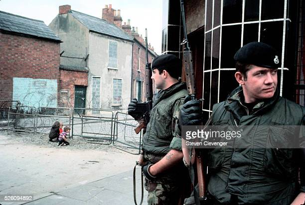 British soldiers pause briefly while on patrol in Cathloic area of Belfast Northern Ireland In the background two children play in rubble next to...