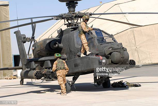 british soldiers perform maintenance on an apache helicopter at camp bastion, afghanistan. - apache helicopter stock pictures, royalty-free photos & images
