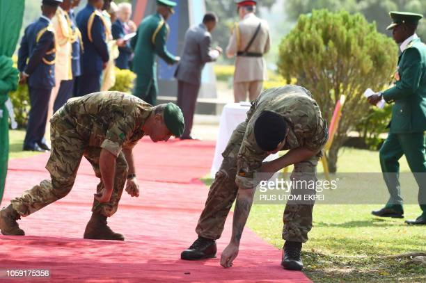 British soldiers pick dirt on the red carpet before the arrival of Britain's Prince Charles at the National Military Cemetery to lay wreath in honour...