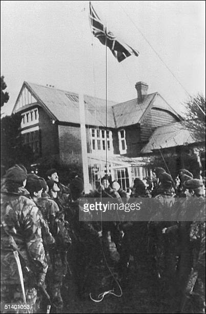 British soldiers raise the Union Jack flag at Government House in Port stanley 17 June 1982 after the surrender of Argentine forces ending the...