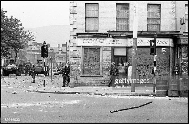 British soldiers retakes a street corner during rioting on the republican Falls Road in Belfast. A resident shelters metres away. 17th September 1976.