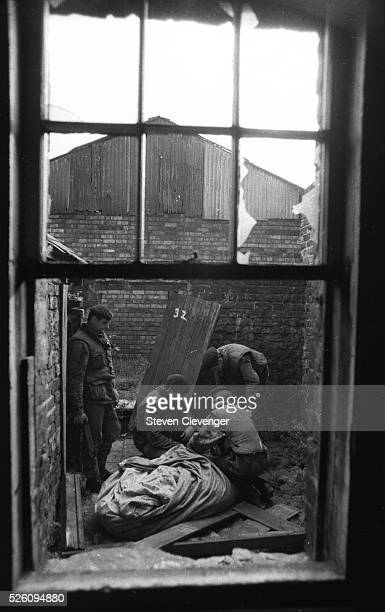 British soldiers search the rear area of an abandoned row house in the Catholic area off Falls Road in Belfast
