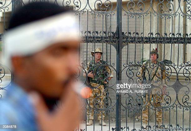 British soldiers stand guard at the headquarters of the British military command controlling southern Iraq during a rally by Iraqi Shiite men in the...