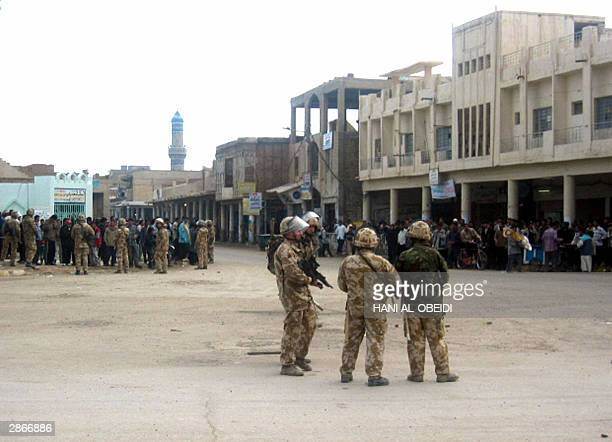 British soldiers stand guard close to government buildings as tensions remain high 13 January 2004 in the southern city of Amara 365 kilometres...