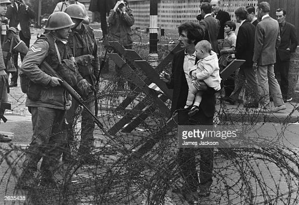 British soldiers stop a man trying to carry his baby through a barbedwire barricade on the Catholic Falls Road area of Belfast