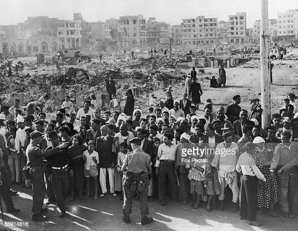British soldiers supervise a crowd in the Arab quarter of Port Said while food is distributed during the Suez Crisis, 12th November 1956.