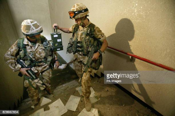 British soldiers use a nerve and blister agent testing kit in a stairwell leading to a flooded room at a building believed to have been used by...