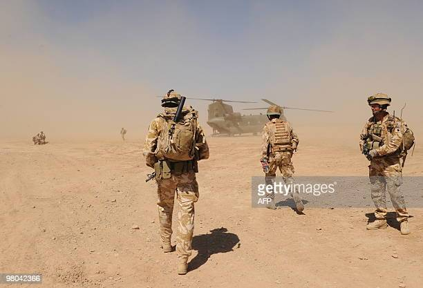 British soldiers walk towards a military helicopter near the Pimon military camp in Nade Ali district of Helmand province on March 25 2010 Britain's...