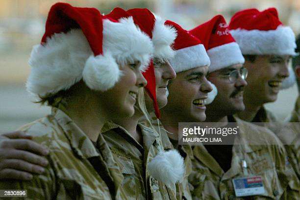 British soldiers wearing Santa Claus hats pose for a picture during a Christmas mass at their base in Basra International Airport, some 500 kms...