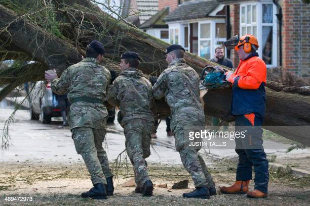British soliders help a tree surgeon remove a fallen tree in Egham west of London on February 15 2014 after high winds brought by a winterstorm...