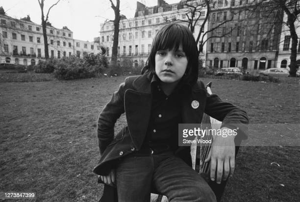 British songwriter, musician, and record producer Ricky Wilde wearing an overcoat a Smiley badge on the lapel, as he poses sitting on the arm of a...