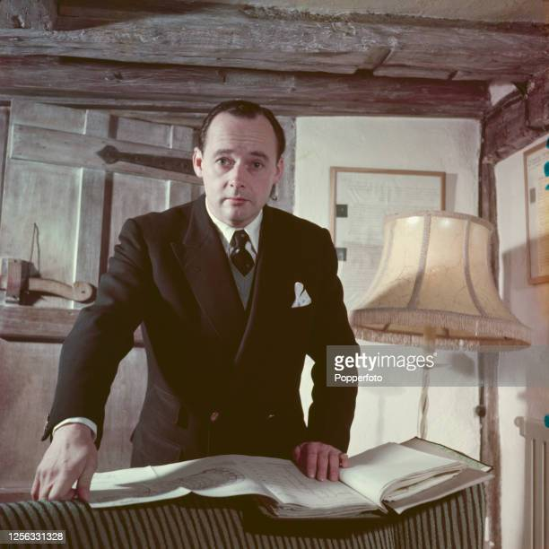 British speed record breaker Donald Campbell posed with a folder of technical documents at his house 'Abbotts' in the village of Leigh in Surrey...