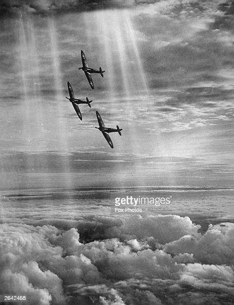 British Spitfires flying in formation through the rays of the sun above the clouds