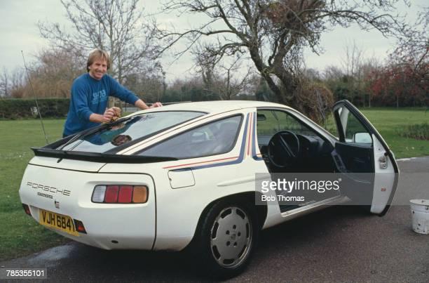 British sportscar racing driver Derek Bell pictured washing his Porsche 928S car at home in West Sussex England on 23rd December 1986 Derek Bell is...