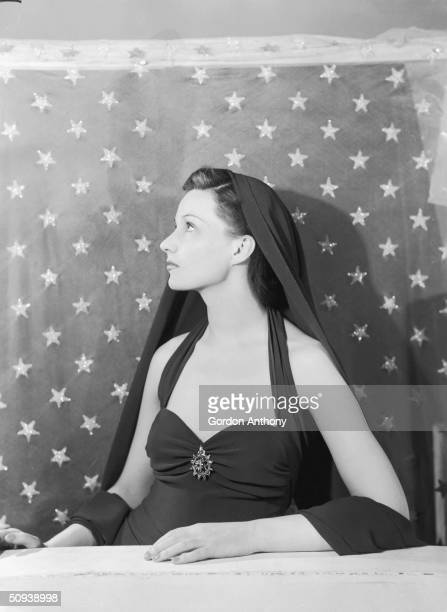 British stage and screen actress Judy Campbell in front of a starry backdrop, circa 1948.