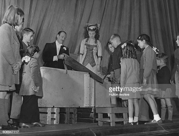 British stage magician Jasper Maskelyne prepares to saw assistant Maisie Wright in half at the Whitehall Theatre in London 1948 Photo by James Jarche...