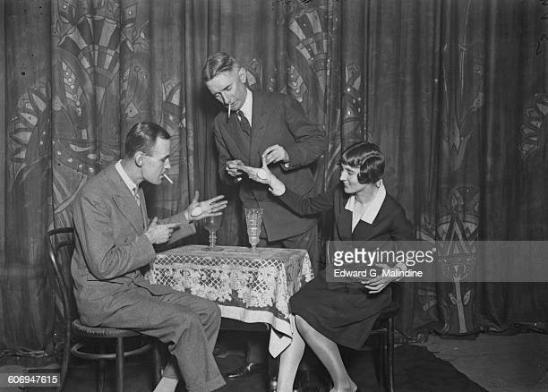 British stage magician Noel Maskelyne and fellow illusionist Oswald Williams teach Noel's sister Mary how to palm objects UK 7th October 1927 Noel...