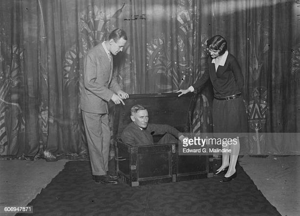British stage magician Noel Maskelyne and his sister Mary perform the famous box trick, by shutting fellow illusionist Oswald Williams in a trunk,...