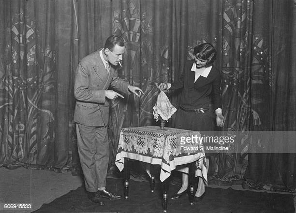 British stage magician Noel Maskelyne watches his sister Mary perform the disappearing water trick, UK, 7th October 1927. Their father was famous...