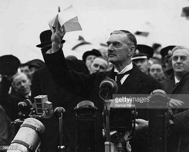 British statesman and prime minister Neville Chamberlain at Heston Airport on his return from Munich after meeting with Hitler making his 'peace in...