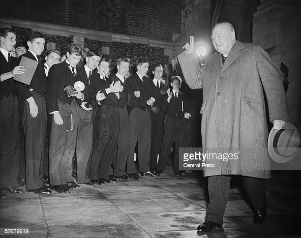 British statesman Winston Churchill gives his victory salute to some of the boys during his annual visit to his old school Harrow 27th November 1953