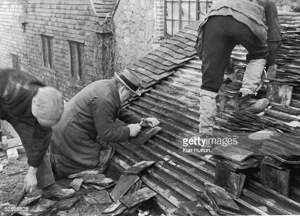 British statesman Winston Churchill helping to lay tiles on the roof of a new cottage at his Chartwell estate in Kent 25th February 1939 Original...
