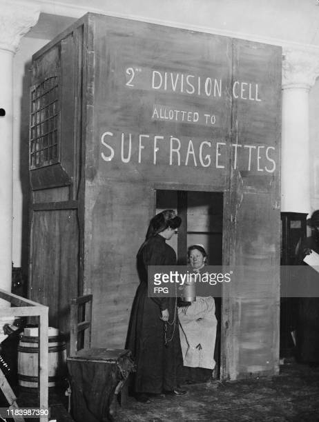 British suffragettes Wilfred Berrager as a 'prisoner' and Nancy Smart as a 'wardress' mimic a scene within a cell 'allotted to suffragettes' at the...