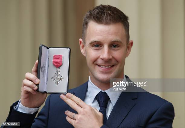 British superbike world champion Jonathan Rea poses with his medal after being appointed a Member of the Order of the British Empire during an...