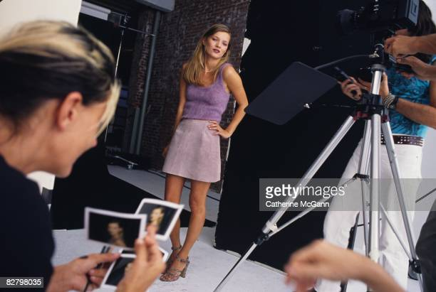 British Supermodel Kate Moss, center, stands with hand on hip as an unidentified makeup artist, foreground, looks through Polaroids during a fashion...