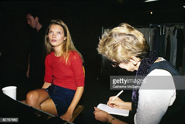British Supermodel Kate Moss, left, rolls her eyes upward as a journalist, right, interviews her and takes notes during a fashion shoot at a photo...