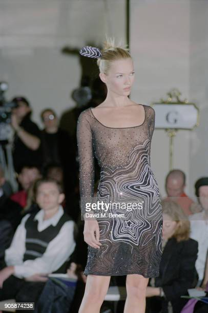 British supermodel Kate Moss wearing dotted transparent dress with stars details with a matching feather in her hair on the catwalk at the Gianni...