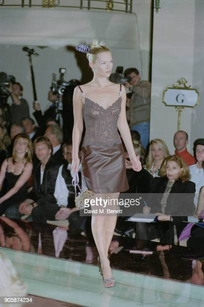 British supermodel Kate Moss wearing lace brown tank top and brown leather skirt while holding a small leopard clutch bag at the Gianni Versace Haute...