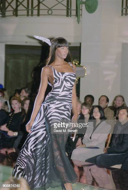 British supermodel Naomi Campbell wearing a full length black lace and zebrastriped dress with a matching feather in her hair on the catwalk at the...