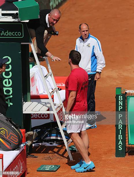 British team captain Leon Smith discusses a point with the chair umpire as he watches Andy Murray of Great Britain during his straight sets defeat in...