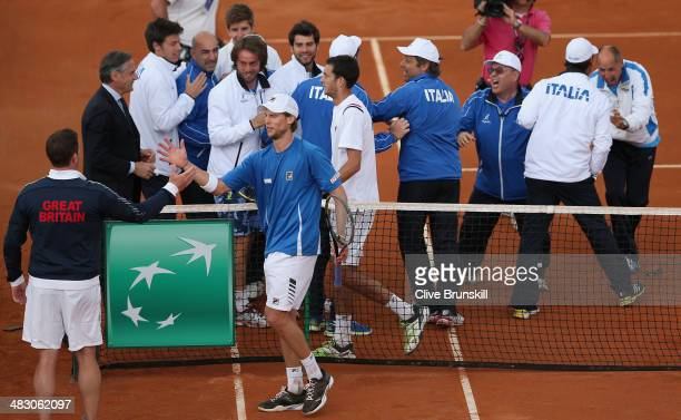 British team captain Leon Smith shakes hands and congratulates Andreas Seppi of Italy after winning the fifth and decisive rubber against James Ward...