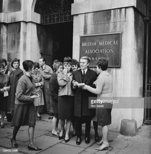 British teen idol singer actor and financial journalist Adam Faith with fans after a meeting at the British Medical Association London UK 21st...