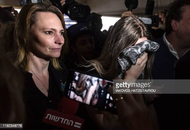 British teenager convicted of falsely accusing a group of Israelis of gang-rape, covers her face as she arrives with her mother to the Famagusta...