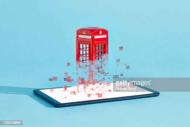 a british telephone box emerging from a digital tablet - richard drury stock pictures, royalty-free photos & images