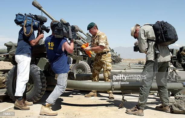 British television crew captures video of Royal Marine Commando Grant Allen from Worcester England as he cleans a 105mm light field gun April 9 2002...