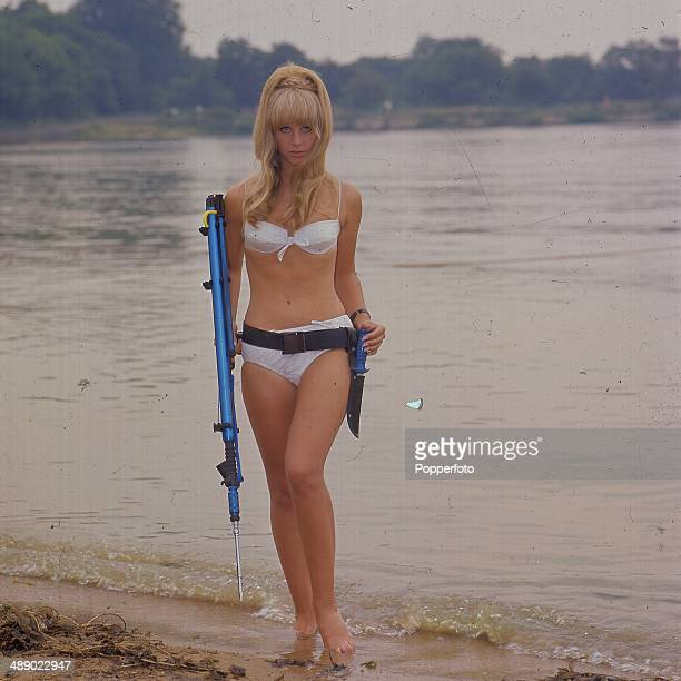 British television hostess and actress Carol Dilworth posed wearing a white bikini and holding a spear gun beside a lake in 1967