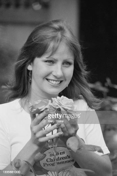 British television presenter and actress Sarah Greene, wearing a 'BBC TV Children's Programmes' t-shirt, smiles as she holds flowers as she unveiled...