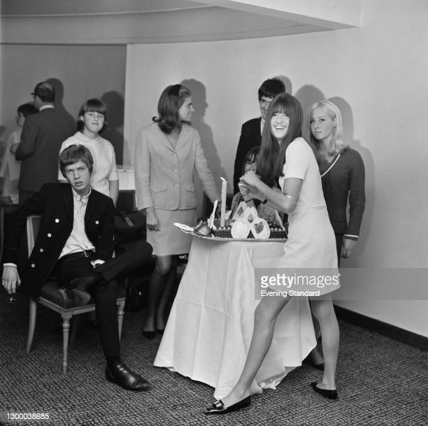 British television presenter Cathy McGowan cuts into a cake at a party with singer Scott Walker of the Walker Brothers, UK, September 1966.