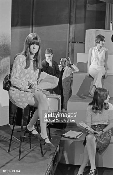 British television presenter Cathy McGowan wearing a minidress with a diamond pattern, sitting on a stool with a script in her hand, among...